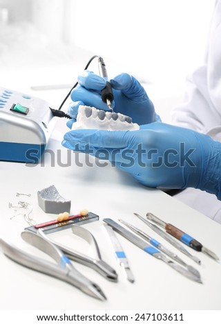 Prosthetics..Prosthetics hands while working on the denture, false teeth, a study and a table with dental tools. - stock photo