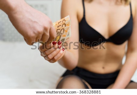 Prostitute takes money for her work. - stock photo