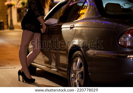 Prostitute talking with client on the street - stock photo