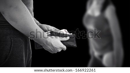 prostitution, paying prostitute with money from wallet, black and white with copy space - stock photo