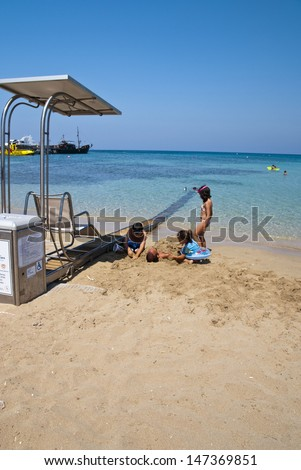 PROTARAS,CYPRUS-JULY 10,2013:New device - care for the convenience and and the pleasure of people with disability,during their summer vacation on the beach in Protaras,Cyprus on july 10,2013
