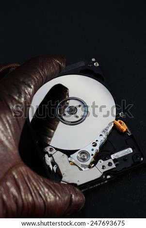 Protect your data, hand with glove over open hard disk drive, stealing information concept - stock photo