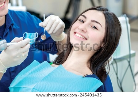Protect your teeth. Patient of a dentist put on safety glasses and looks with a smile directly at the camera - stock photo
