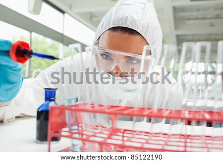 Protected female science student dropping blue liquid in a test tube in a laboratory - stock photo