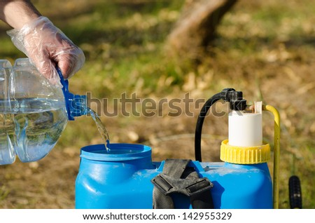 Protected hands filling a pesticide sprayer - stock photo