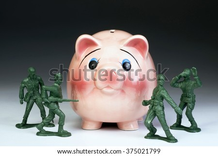 Protecting American money in the piggy bank with green toy soldiers. - stock photo