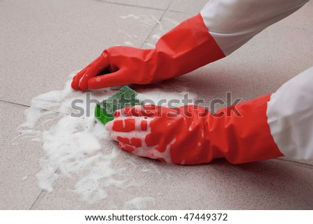 protecting hand from detergents, washing floor by cleaning sponge - stock photo