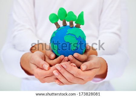 Protecting our environment concept - clay earth with trees held by child and adult hands - stock photo