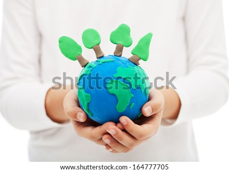 Protecting the forests and ecology concept - child hand holding earth globe with trees - stock photo