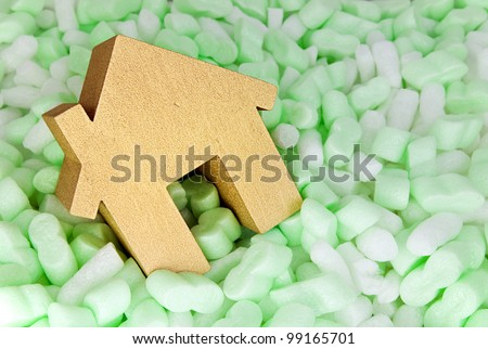 protecting your property, gold house in foam protective packaging - stock photo