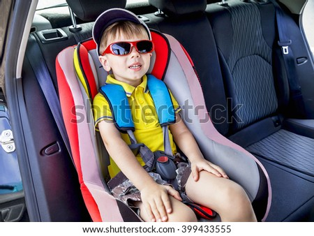 Protection in the car. Caucasian child in the sunglasses is sitting and fastening with security belt in safety car seat (chair). Toddler boy is ready to the trip. Vehicle and transportation concept. - stock photo