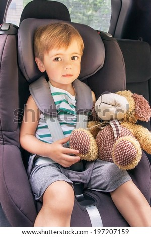 Protection in the car. Caucasian child is sitting and fastening with security belt in safety car seat (chair).Toddler boy is playing with toy (dog) in the car.  Vehicle and transportation concept. - stock photo