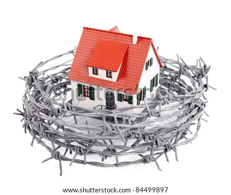 Protection of a miniature house with a barbed wire, concept - stock photo