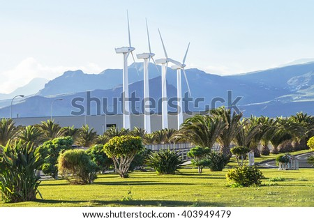 Protection of nature. Wind turbines against mountains landscape. Windmills located outside the city. Electric generator is alternative energy resources. Ecology concept. Spain. Copy space. - stock photo
