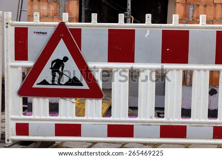 protection of the road at a construction site. sign with construction worker - stock photo