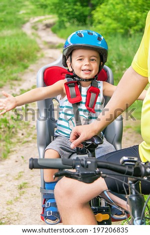 Protection on the bicycle. Caucasian joyful happy child have biking helmet. The little cute  boy is in the bicycle chair (seat) during bicycle ride. Summer travel concept. Close up.  - stock photo