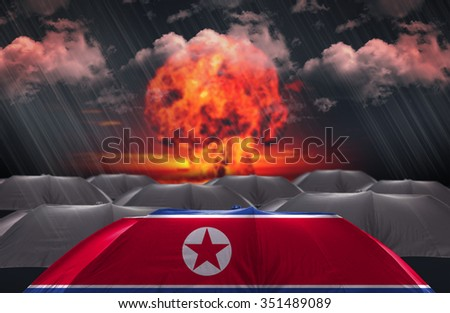 Protection Umbrella with flag of North Korea on a war background - stock photo