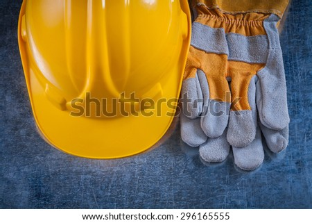 Protective building helmet and safety working gloves on scratched metallic surface construction concept. - stock photo