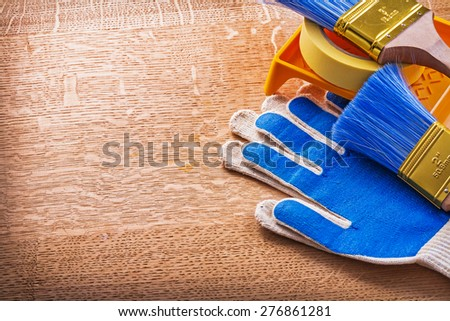 Protective gloves duct tape paint tray and brushes on wooden board construction concept