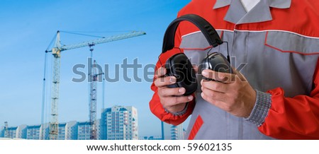 protective headphone at man hands on building background - stock photo