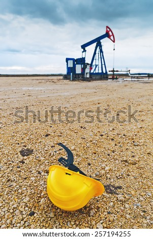 Protective Helmet and Pumpjack Oil Pump operating on natural gas in the field pumping from the oil well. - stock photo