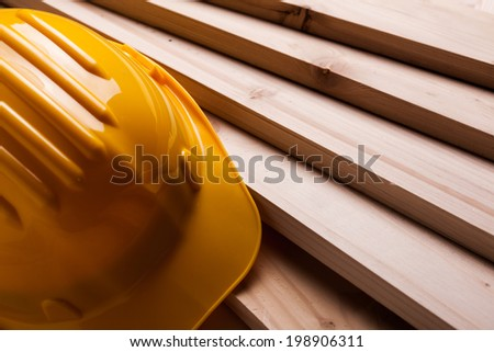 Protective helmet and wooden planks. - stock photo