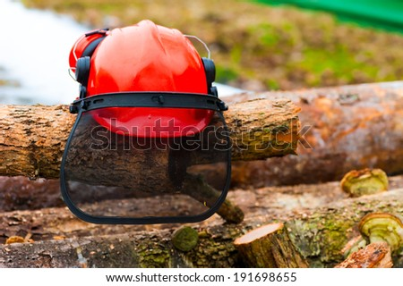 protective helmet lying on the logs in the forest - stock photo