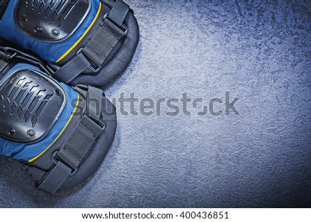 Protective knee pads on black background construction concept. - stock photo