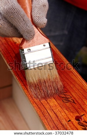Protective lacquer coating wood surfaces with a construction brush. Do it yourself. DIY - stock photo