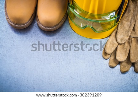 Protective leather gloves waterproof safety boots building helmet and plastic goggles on scratched metallic background construction concept. - stock photo