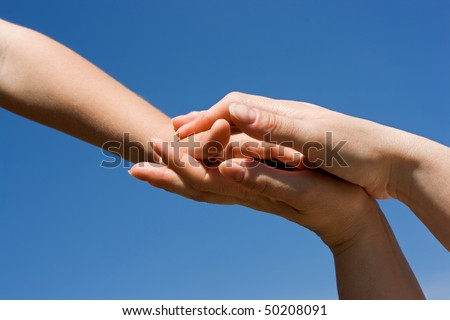 Protective mother's hands holding her children - stock photo