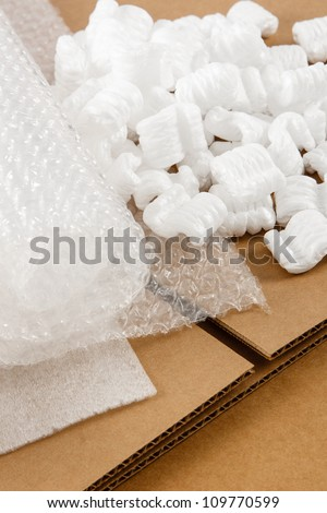 Protective packaging materials atop brown corrugate boxes show an assortment of shipping supplies - stock photo