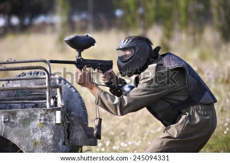 Protective sport player in uniform and mask Aiming gun, behind a jeep - stock photo