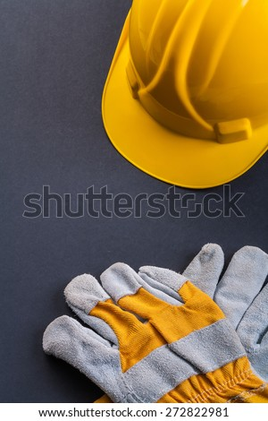 protective working gloves and yellow helmet on black background  - stock photo