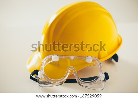 Protective workwear: yellow hardhat and protective glasses for construciton workers.