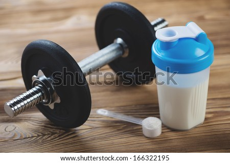 Protein shake and a dumbbell on a wooden surface - stock photo