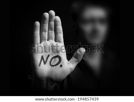 Protest concept.Close-up of palm with male silhouette on black background - stock photo