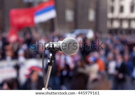 Protest. Public demonstration. Microphone in focus against blurred crowd.