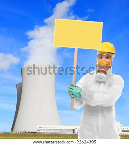 Protester in gas mask with blank protest sign against nuclear power plant. Picture with room for your text. - stock photo