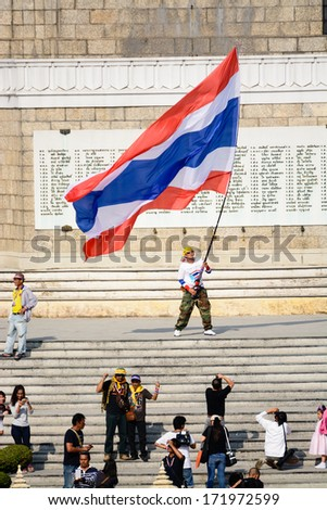 "Protester waving Thai flag to protest against the government corruption in  ""Shut down Bangkok"" campaign. on January 18,2014 in BANGKOK,THAILAND."