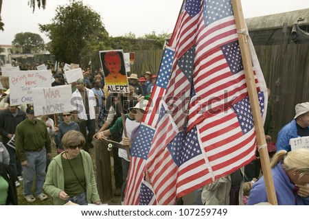 Protesters march with US Flag against President George W. Bush and the Iraq war at an anti-Iraq War protest march in Santa Barbara, California on March 17, 2007 - stock photo