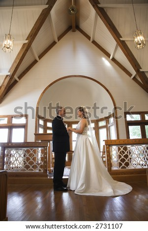 Protrait of bride and groom holding hands at the alter of a church. - stock photo