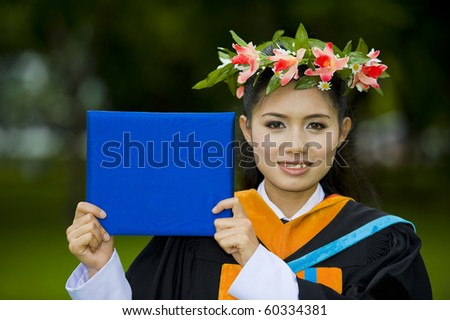 proud asian student showing on her graduation day - stock photo