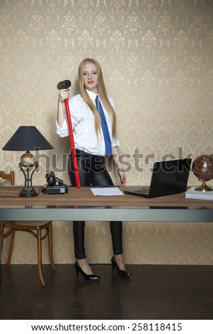 proud business woman with a big hammer - stock photo