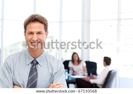 Proud businessman posing in front of his team while working in the background