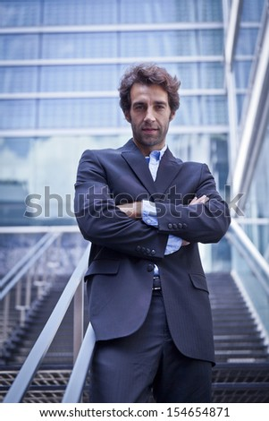 Proud businessman standing in front of his office - stock photo