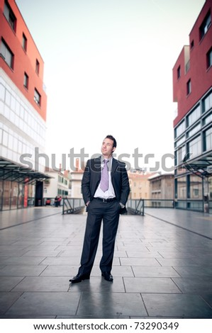 Proud businessman standing in the street looking up - stock photo