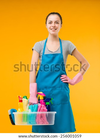 proud caucasian woman standing and holding cleaning supplies against yellow background - stock photo