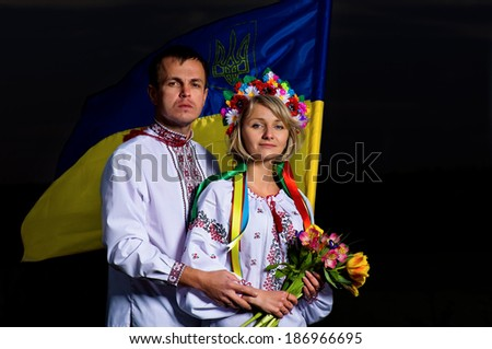 Proud couple in the Ukrainian national costumes with Ukrainian flag - stock photo