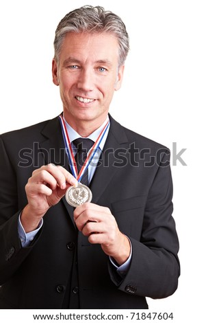 Proud elderly business man showing a silver medal around his neck - stock photo